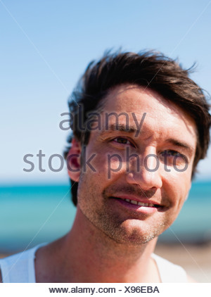 man on beach looking at viewer - Stock Photo