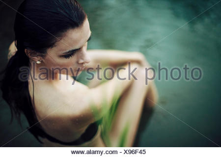 young woman sits in the water - Stock Photo