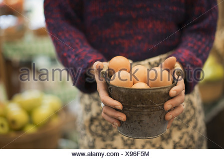 Organic Farmer at Work A woman carrying a container of eggs - Stock Photo