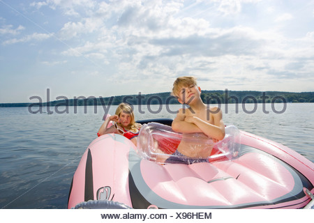 Two children in an inflatable raft on a lake - Stock Photo