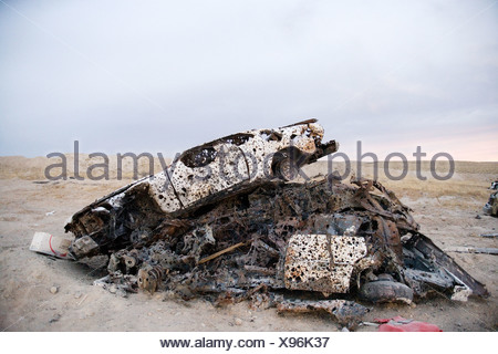Car with bullet holes used for target practice - Stock Photo