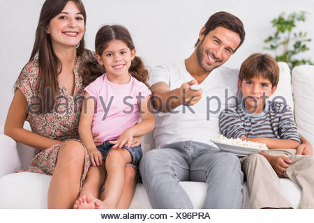 Happy family watching television together - Stock Photo
