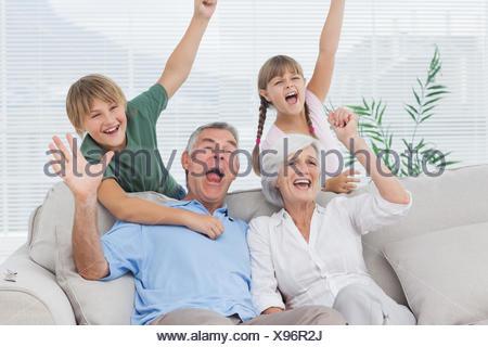 Grandparents and grandchildren raising arms - Stock Photo