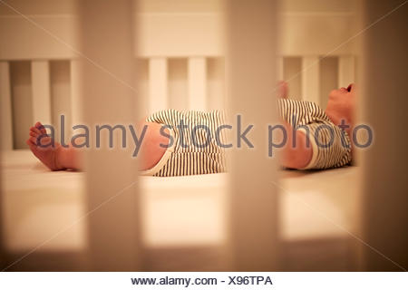 Baby boy asleep in crib with mouth open - Stock Photo
