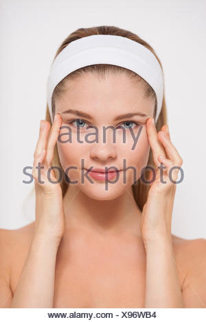 Woman touching temples with fingers - Stock Photo