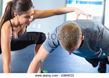 Couple helping each other in gym - Stock Photo
