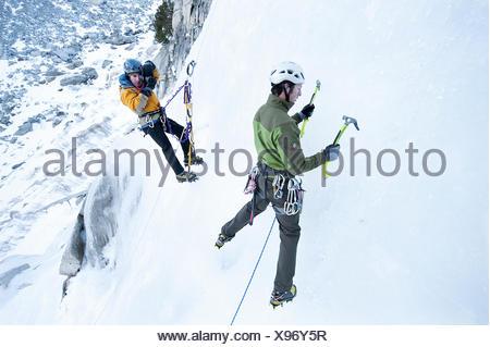 A photographer photographs an ice climber in Calif. - Stock Photo
