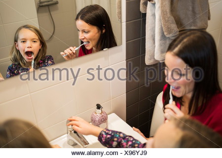 Mother and daughter brushing teeth in bathroom - Stock Photo