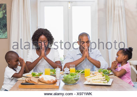 Happy family saying grace before meal - Stock Photo