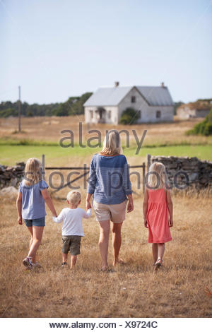 Sweden, Gotland, Faro, Mother with son (2-3) and daughters (8-9, 10-11) walking in farm yard - Stock Photo
