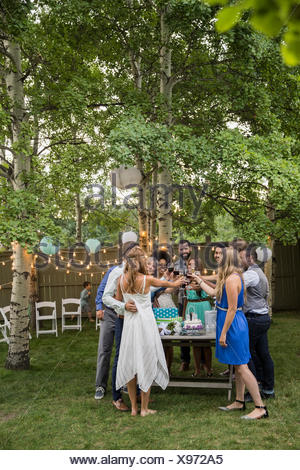 Bride, groom and wedding guests toasting wine reception - Stock Photo