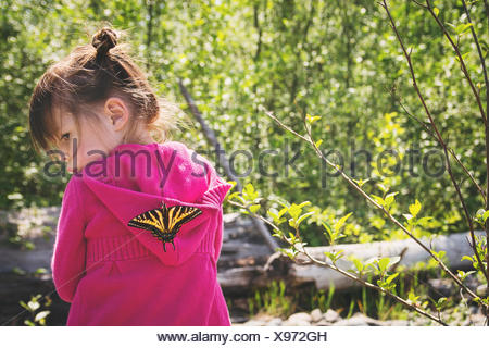 Young girl with a butterfly on her back - Stock Photo