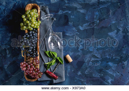 Variety of three type fresh ripe grapes dark blue, red and green in wooden bowl with empty laying wine glass, old corkscrew and green leaves over blue - Stock Photo