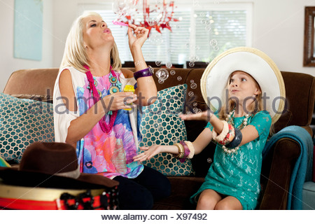 Mother and daughter blowing bubbles in sitting room - Stock Photo
