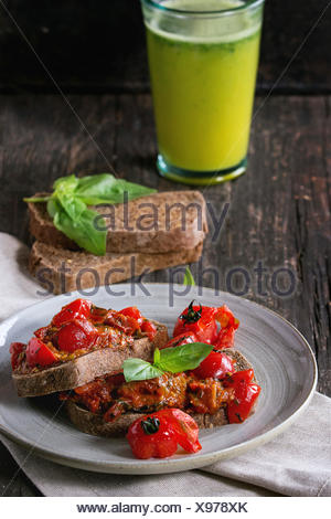 Italian tomato bruschetta with baked cherry tomatoes and fresh basil, served on gray ceramic plate with textile napkin and glass - Stock Photo