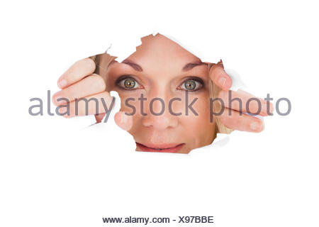 Woman looking through torn paper