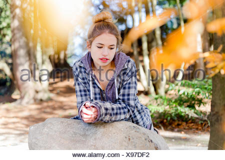 This young teenage girl hangs out alone in a park, sitting on a rock in a thoughtful disengaged position thinking to herself - Stock Photo