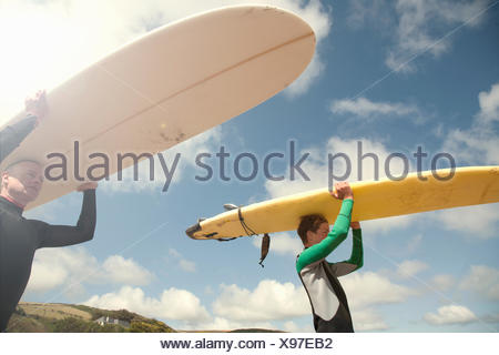 Man and teenage boy carrying surfboards - Stock Photo