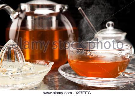 Dampfender Tee in Teeservice aus Glas - Stock Photo