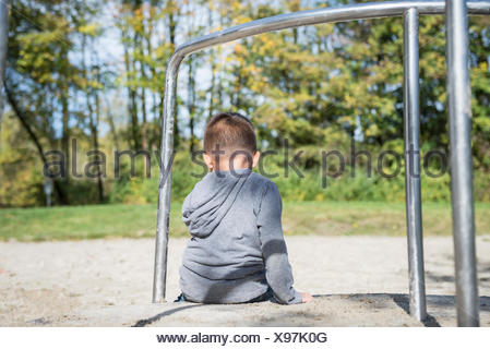Small lonely boy sitting alone in playground - Stock Photo