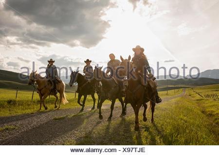 Female ranchers horseback riding on remote sunny road - Stock Photo