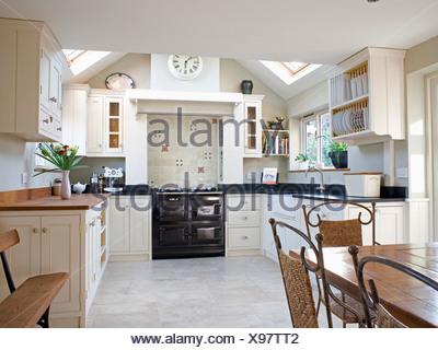 Black Aga oven and limestone flooring in barn conversion kitchen ...
