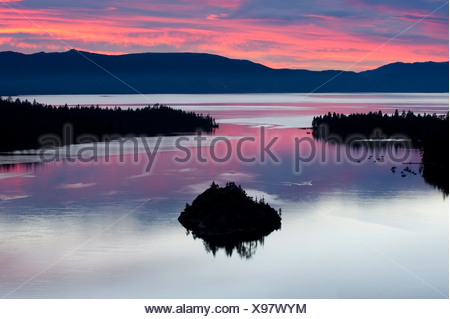A silhouette of Fannette Island in Emerarld Bay during a beautiful sunrise in Lake Tahoe, CA. - Stock Photo
