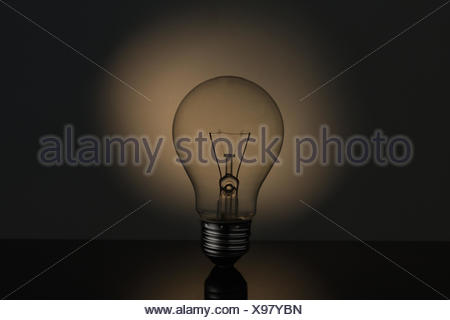Big light bulb standing in sepia tones on reflective black surface - Stock Photo
