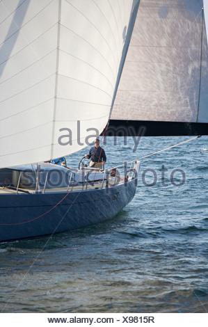 A crew races a modern ocean-going sailing yacht. - Stock Photo