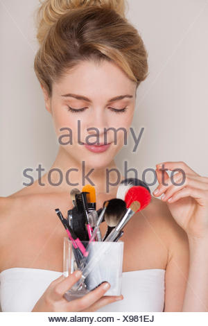 Beautiful woman holding assorted makeup brushes - Stock Photo