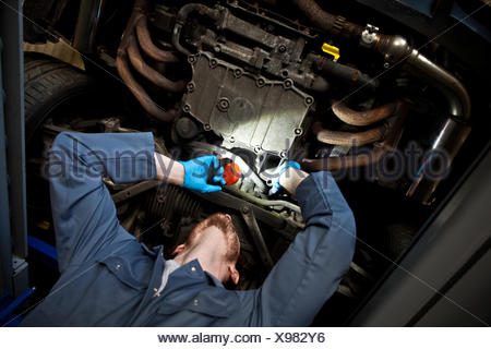 Male mechanic holding torch, looking under car - Stock Photo