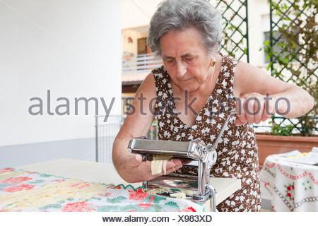 Older woman making pasta with roller - Stock Photo