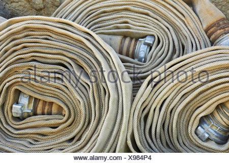 Old rolled fire hoses with nozzles - Stock Photo