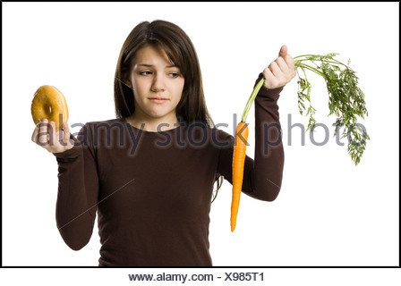 young woman choosing between a carrot and a donut - Stock Photo