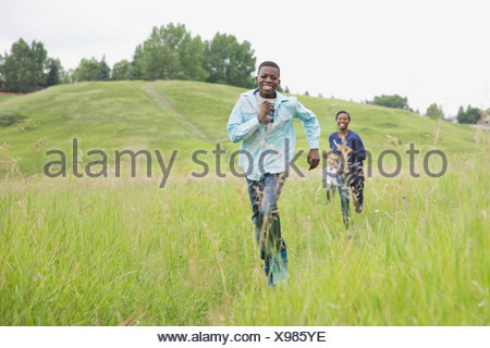Happy siblings running through field - Stock Photo