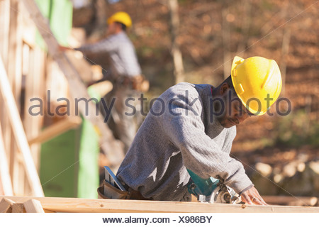 Carpenters cutting rafter - Stock Photo