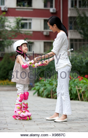 Chinese mother and daughter in rollerblades - Stock Photo