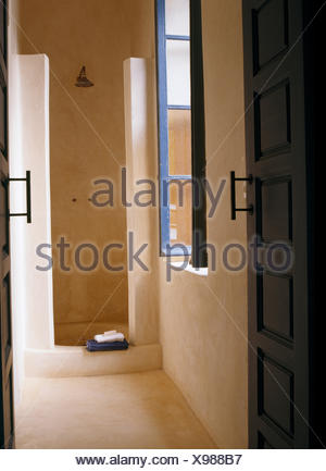 Polished concrete walls in shower in modern Moroccan bathroom - Stock Photo