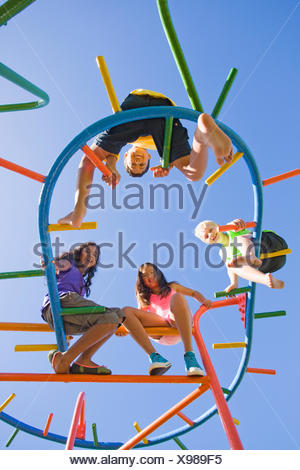 Smiling children sitting on monkey bars at playground - Stock Photo
