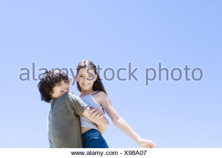 Teenage boy picking up little sister, hugging, low angle view - Stock Photo