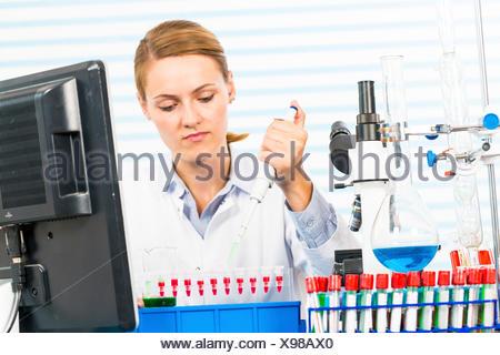 MODEL RELEASED. Female chemist using pipette in laboratory. - Stock Photo