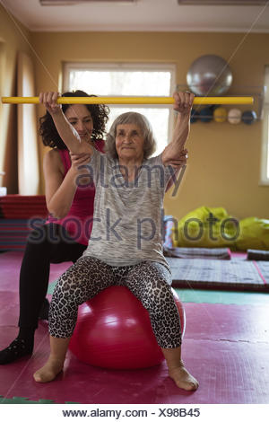 Female therapist assisting senior woman with exercise stick and exercise ball - Stock Photo