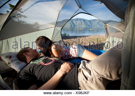 A young couple camping talk in their tent next to a lake in Idaho. - Stock Photo