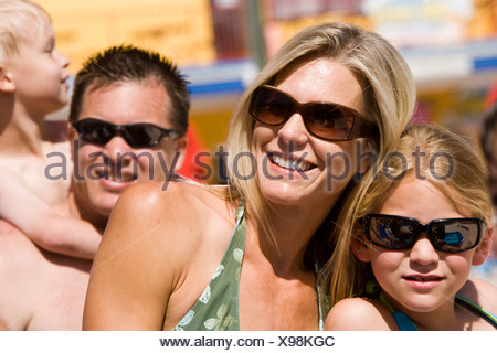 Headshot of family wearing swimsuits and sunglasses on sunny day - Stock Photo