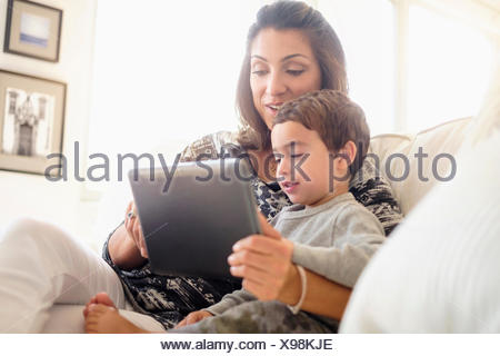 Mother reading with son (2-3) on sofa - Stock Photo
