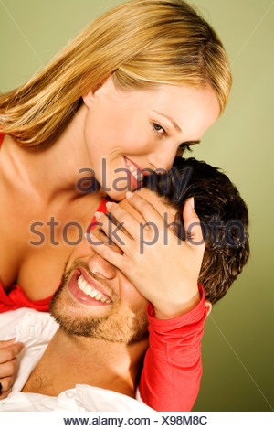 Young smiling woman with hand over man's eyes - Stock Photo