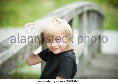 Portrait of little boy standing on wooden boardwalk - Stock Photo