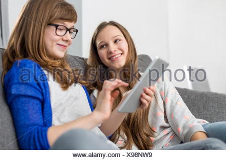 Happy girl looking at sister using digital tablet on sofa at home - Stock Photo