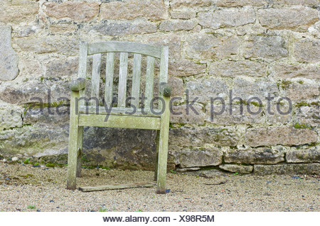 Old chair in front of stone wall - Stock Photo