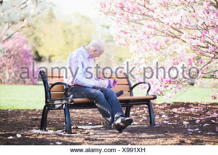 Grandfather and granddaughter together on park bench - Stock Photo